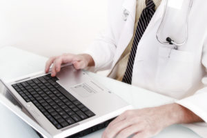 Doctor in white coat at a laptop computer