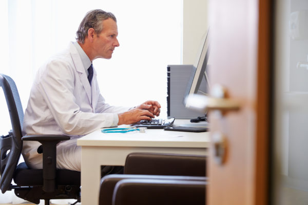 Male Doctor In Office Working At Computer